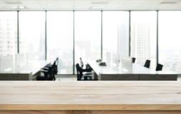 Tabela de madeira vazia com opinião do escritório da sala do borrão e da cidade da janela Foto de Stock Royalty Free