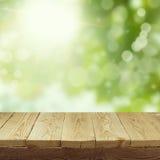 Tabela de madeira vazia da plataforma com fundo do bokeh da folha para a montagem da exposição do produto Mola ou verão imagens de stock