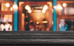 Tabela de madeira vazia do foco seletivo na frente do fundo festivo borrado sumário com bokeh do fundo do mercado da noite para o fotografia de stock