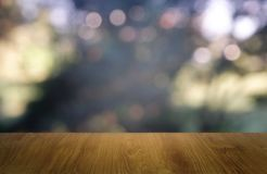 Tabela de madeira vazia na frente do verde borrado abstrato do fundo do jardim e da casa Para a exposição do produto da montagem  foto de stock royalty free
