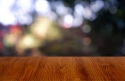 Tabela de madeira vazia na frente do verde borrado abstrato do fundo do jardim e da casa Para a exposição do produto da montagem  foto de stock