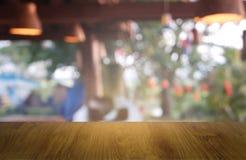 Tabela de madeira vazia na frente do verde borrado abstrato do fundo do jardim e da casa Para a exposição do produto da montagem  fotos de stock royalty free