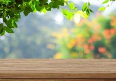 Tabela de madeira vazia sobre árvores borradas com fundo do bokeh imagem de stock royalty free