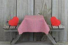 Tabela de piquenique com corações e toalha de mesa vermelhos Fotografia de Stock Royalty Free
