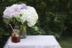 Tabela de piquenique do verão com flores Fotos de Stock