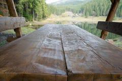 Tabela de piquenique de madeira pelo lago fotografia de stock