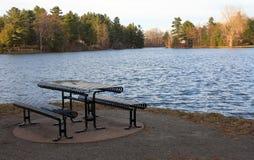 Tabela de piquenique na água azul dos lagos park Foto de Stock