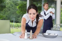 Tabela de sorriso do ajuste da empregada de mesa no restaurante imagem de stock royalty free
