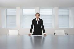 Tabela de Standing At Conference da mulher de negócios Imagens de Stock