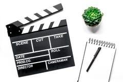 Tabela de trabalho do produtor Clapperboard e caderno do filme na opinião superior do fundo branco Foto de Stock Royalty Free