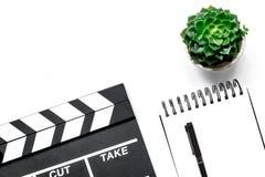 Tabela de trabalho do produtor Clapperboard e caderno do filme no copyspace branco da opinião superior do fundo Foto de Stock Royalty Free
