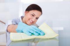 Tabela de vidro de limpeza da empregada doméstica Fotos de Stock