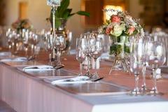 Tabela decorada com as flores no copo de água Fotos de Stock