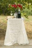 Tabela decorada com a garrafa do vinho tinto, dos vidros e do ramalhete das flores em um casamento judaico tradicional em Ojai, C Imagens de Stock Royalty Free