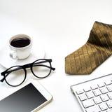Tabela desktop do escrit?rio branco moderno com uma x?cara de caf?, a gravata e as outras fontes Vista superior com espa?o da c?p fotografia de stock