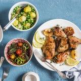 Tabela do almoço Galinha cozida tomilho do limão, batatas fervidas com ervilhas verdes, salada com lentilhas e tomates em um fund Foto de Stock