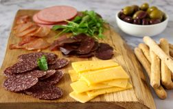 Tabela do aperitivo para o vinho ou a cerveja com salsichas, carne secada e queijo, servidos com grissini, ervas e azeitonas fotos de stock