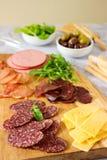 Tabela do aperitivo para o vinho ou a cerveja com salsichas, carne secada e queijo, servidos com grissini, ervas e azeitonas foto de stock