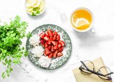 Tabela do café da manhã ou de petisco - morangos frescas, merengue, chá verde com limão Da casa vida acolhedor ainda em um fundo  Fotografia de Stock Royalty Free