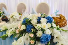 A tabela do casamento dos recém-casados é decorada com os ramalhetes de flores frescas Foto de Stock