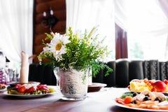 Tabela do casamento no restaurante com composição da flor fotos de stock