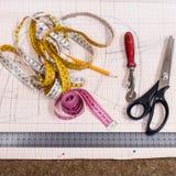 Tabela do corte com pano, lápis, teste padrão, ferramentas Fotos de Stock Royalty Free