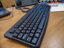 Tabela do escritório com computador preto o teclado prendido closeup fotografia de stock