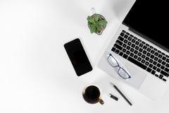 Tabela do escritório com laptop, smartphone, pena, caderno e café no fundo/zombaria brancos puros isolados do portátil e da tabul Fotos de Stock Royalty Free