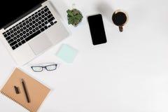 Tabela do escritório com laptop, smartphone, pena, caderno e café no fundo/zombaria brancos puros isolados do portátil e da tabul Fotos de Stock