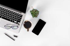 Tabela do escritório com laptop, smartphone, pena, caderno e café no fundo/zombaria brancos puros isolados do portátil e da tabul Foto de Stock
