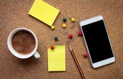 Tabela do escritório com o copo do bloco de notas, do smartphone e de café fotografia de stock royalty free