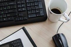 Tabela do escritório com o rato e o café do teclado do caderno Imagem de Stock Royalty Free