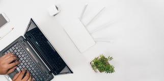 Tabela do escritório com roteador do wifi, computador e opinião superior das fontes Foto de Stock Royalty Free
