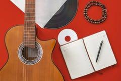 Tabela do escritor da música um espaço de trabalho com a guitarra acústica do músico e o papel do bloco de notas fotografia de stock