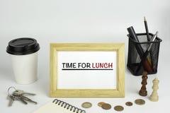 Tabela do escritório com quadro de madeira com texto - hora para o almoço Fotografia de Stock Royalty Free