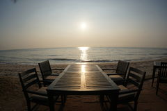 A tabela do jantar no por do sol ou no nascer do sol na praia Imagem de Stock Royalty Free