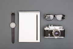 Tabela do journalista ou do blogger - caderno, lápis, câmera e vidros vazios espirais no fundo cinzento, vista superior fotos de stock royalty free
