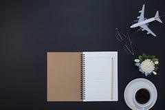 Tabela do preto da mesa de escritório com pena e caderno, copo de café airplan Imagem de Stock Royalty Free