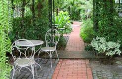 A tabela e as cadeiras brancas do ferro forjado no jardim tropical com tijolos pavimentaram a passagem Imagem de Stock Royalty Free