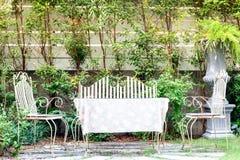 A tabela e as cadeiras do vintage ajustaram-se em um jardim Imagem de Stock Royalty Free