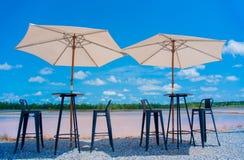 A tabela e as cadeiras e os guarda-chuvas tomam a fotografia que olha acima fotografia de stock royalty free