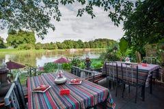 Tabela e assentos do restaurante do beira-rio durante o por do sol Imagens de Stock Royalty Free