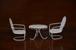 Tabela e cadeiras brancas no assoalho e na parede de madeira fotografia de stock