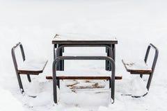 Tabela e cadeiras cobertas na neve Fotografia de Stock