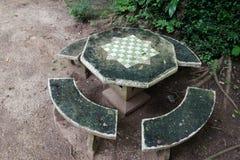 Tabela e cadeiras concretas com placa de xadrez fotografia de stock