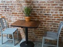 Tabela e cadeiras contra uma parede de tijolo Foto de Stock Royalty Free