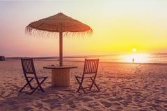 Tabela e cadeiras de madeira com o guarda-chuva na praia Foto de Stock Royalty Free