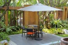 Tabela e cadeiras do jardim do Rattan, jantando a cadeira de jardim exterior no jardim, mobília no pátio moderno imagens de stock royalty free