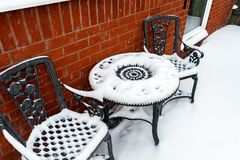 Tabela e cadeiras exteriores do quintal em um pátio coberto com uma camada grossa de neve após a queda de neve em Devon, Inglater foto de stock royalty free