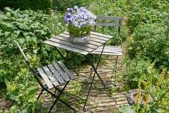 Tabela e cadeiras francesas dos restaurantes em um jardim fotos de stock royalty free